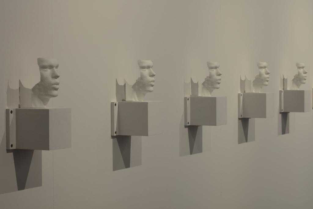 Mehrer Büsten – 3D-Drucke der Stimmbänder der Künstler – hängen nebeneinander an einer Wand.