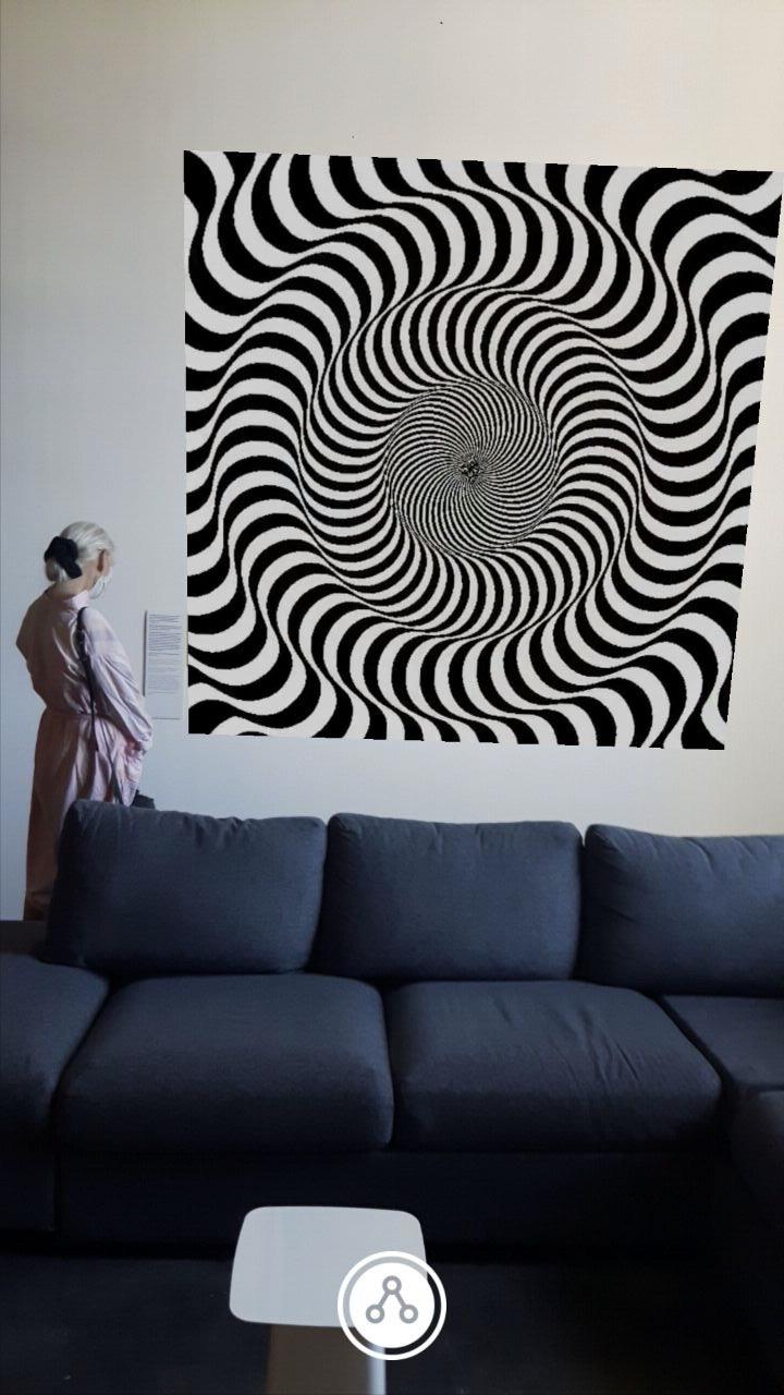 A woman stands behind a sofa, in front of a picture. The picture shows an optical illusion of black and white lines that simulate movement to the eye.