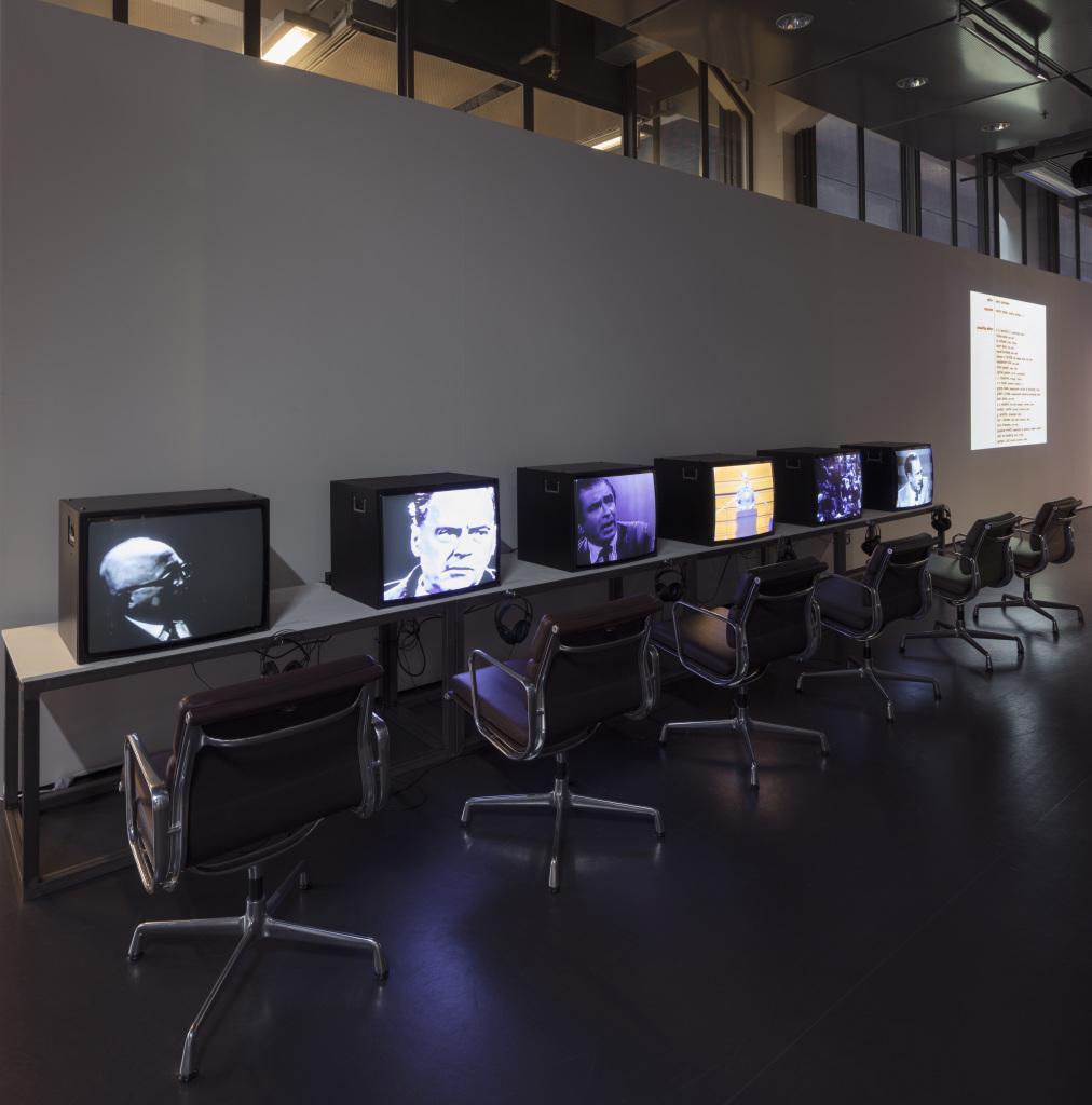 An einer Wand, ein langer Tisch mit sechs Fernsehern, auf denen Unterschiedliche Videos laufen. Dazu jeweils Kopfhörer und davor schwarze Stühle.