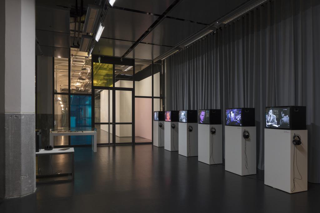 Hinten links eine Glastür in Glaswand. Auf der rechten Seite vor einem grauen Vorhang stehen sechs weiße Podeste mit Fernsehern, auf denen unterschiedliche Videos laufen. Dabei hängen Kopfhörer.