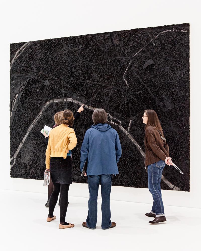 Zu sehen sind vier Personen, die vor einem dreidimensionalen, an der Wand hängenden Bild befinden. Das Bild ähnelt einer Stattkarte, die gänzlich schwarz eingefärbt und von wenigen weißen Linien durchzogen ist