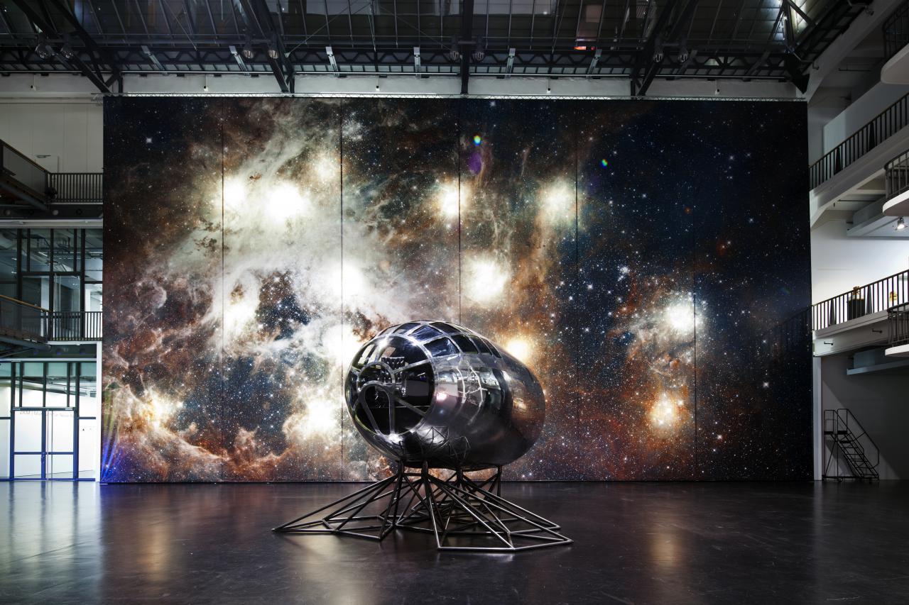 Zu sehen ist ein kleines, silbernes Gestellt vor einer großen Leinwand mit dem Motiv einer Galaxie, das an eine Raketenspitze erinnert.