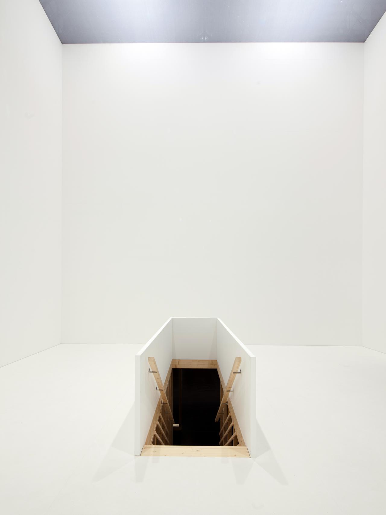 Zu sehen ist ein weißer Raum, der einen Treppenabgang in der Mitte aufzeigt.