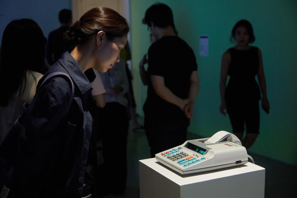 Foto der Ausstellung »Open Codes. Connected Bots«. Ein alter Taschenrechner mit Thermopapier-Rolle rechnet um Bitcoins zu generieren.