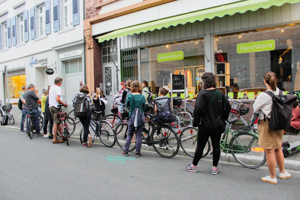 Eine Gruppe Leute versammelt sich mit ihren Fahrrädern vor einem Schaufenster