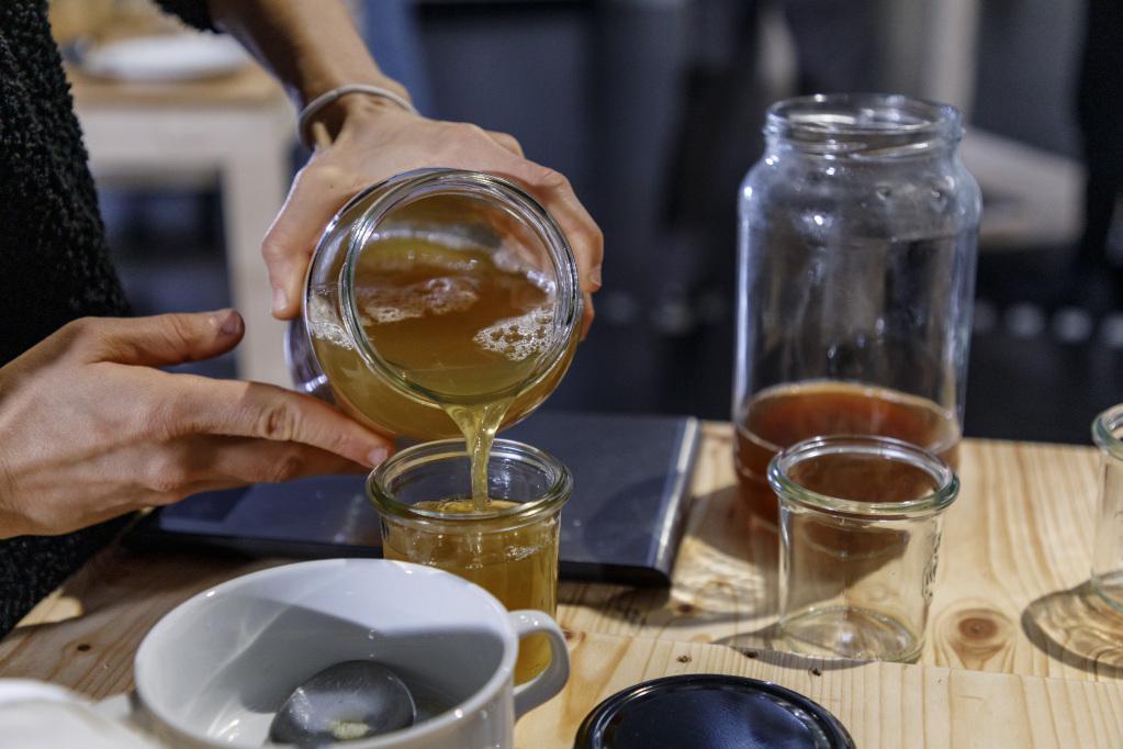Aus einem Einmachglas wird eine Flüssigkeit in ein Glas auf einem Tische gefüllt. Auf dem Tisch stehen weitere Gläser und Schüsseln.