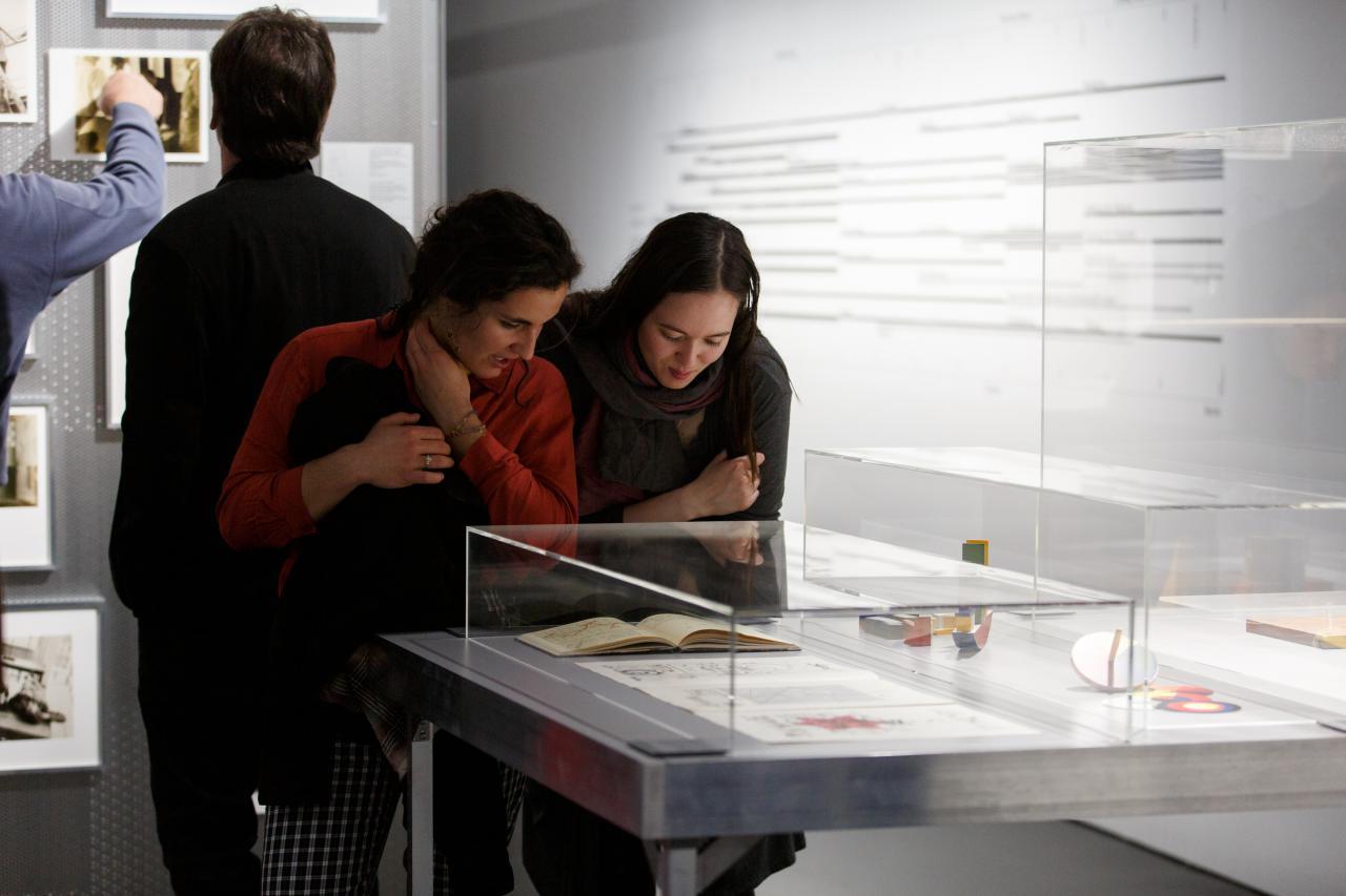 Zu sehen sind zwei Frauen, die sich über eine Vitrine in der Ausstellng beugen und das ausgestellte Buch genauer betrachten.