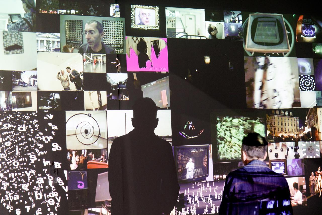 Zu sehen ist eine Video-Installation. Es werden viele kleinere Bilder auf eine Wand projiziert, wobei ein Mosaikartiges Bild entsteht. Davor steht ein betrachtender Mann. Er wirft einen auffälligen Schatten auf die Wand.