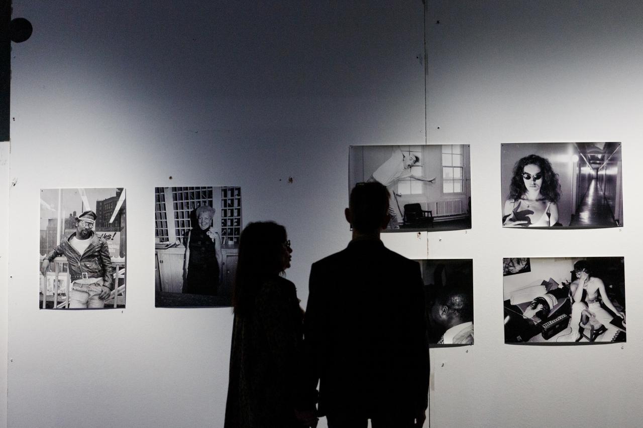 Zwei Personen, die nur als Schatten zu erkennen sind, stehen vor einer Wand mit mehreren Schwarz-Weiß-Fotografien.