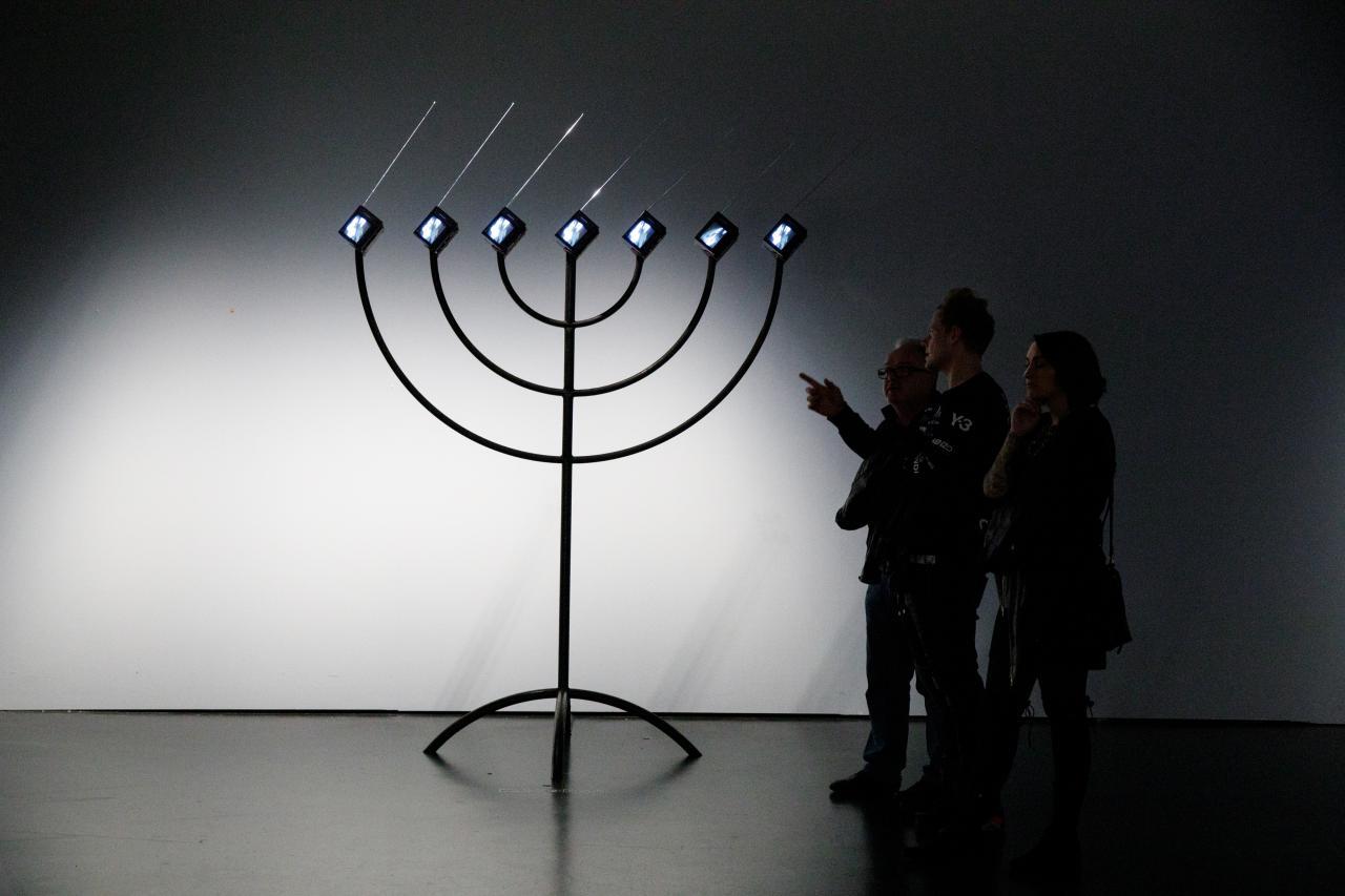 Zu sehen ist eine große, schwarze Menorah, die anstelle von Kerzen sieben kleine Bildschirme, mit nach rechts gerichteten Antennen, hat. Auf der rechten Seite stehen drei Personen, die sie betrachten. Eine der Personen zeigt auf die Installation.