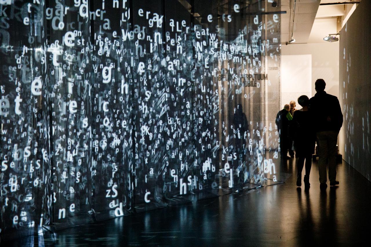 Das Bild zeigt eine große Anzahl von herabhängenden, durchsichtig-schwarzen Vorhängen, auf denen viele leuchtene Buchstaben projiziert werden. Zwei Personen laufen rechts daran vorbei.