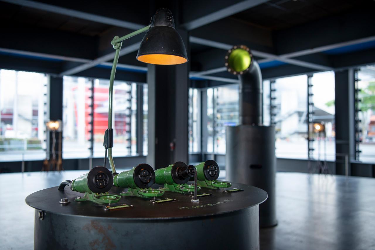 Unter einer Lampe liegen 3 Röhrensteckdosen auf einem metallenen Pult in einem verglasten Ausstellungsraum.