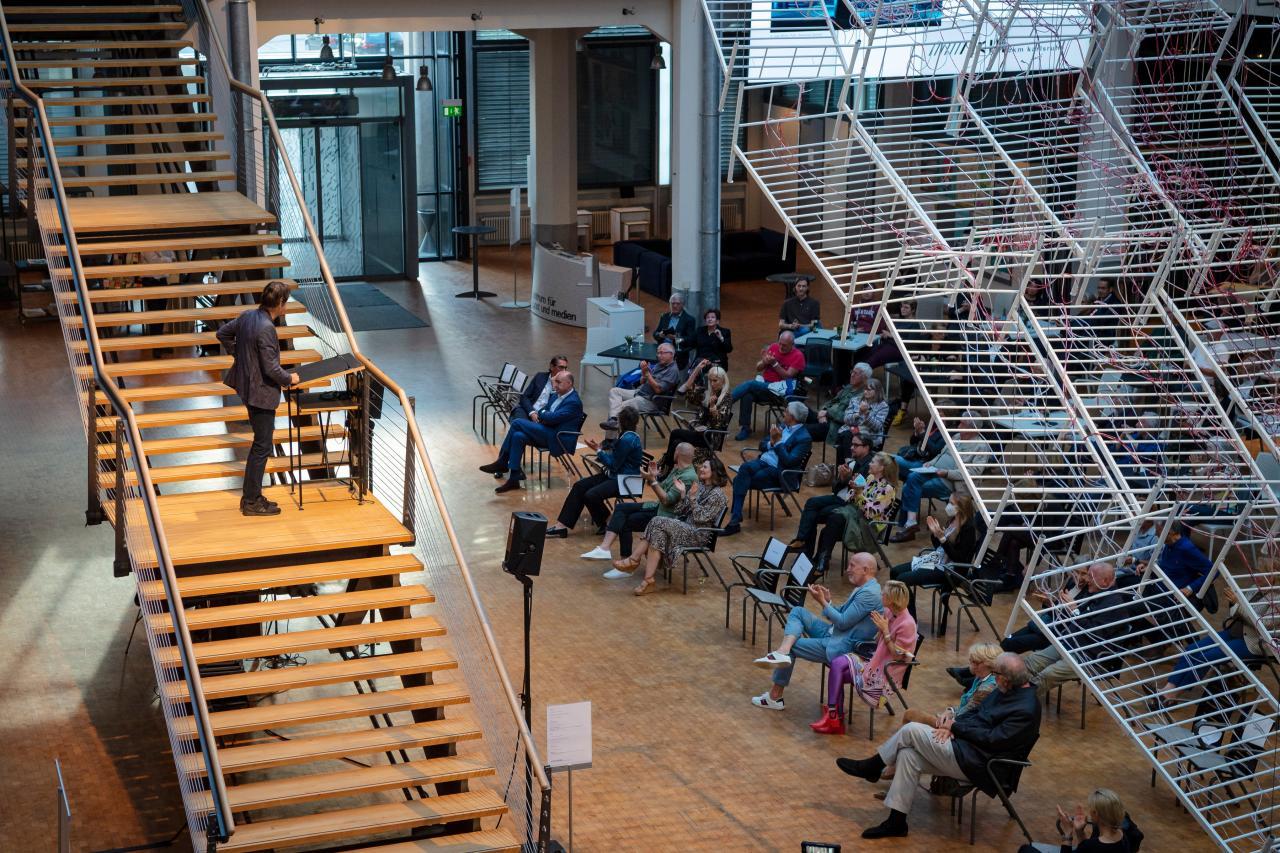 Der Künstler Jean-Remy spricht auf der Treppe im ZKM-Foyer zu den Besucher:innen während der Ausstellunsgeröffnung. Die Besucher sitzen auf Stühlen mit Abstand und hören zu. Über ihnen hängt eine Installation aus Bettengestellen.
