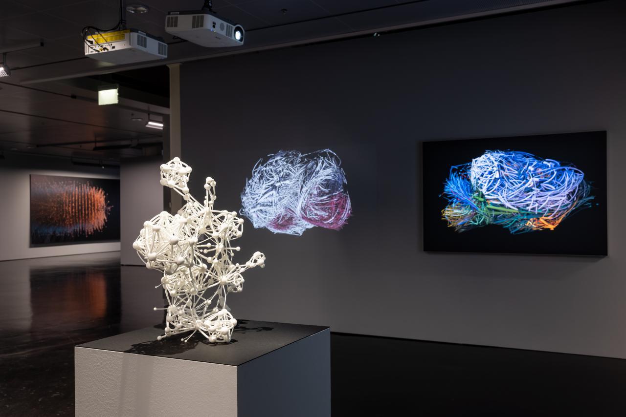 Im Vordergrund steht eine mittelgroße Skulptur, die ein Netzwerk mit vielen Knotenpunkten zeigt. Hinter ihr sind Projektionen von Netzwerken in Form eines Mäusegehirns zu sehen.