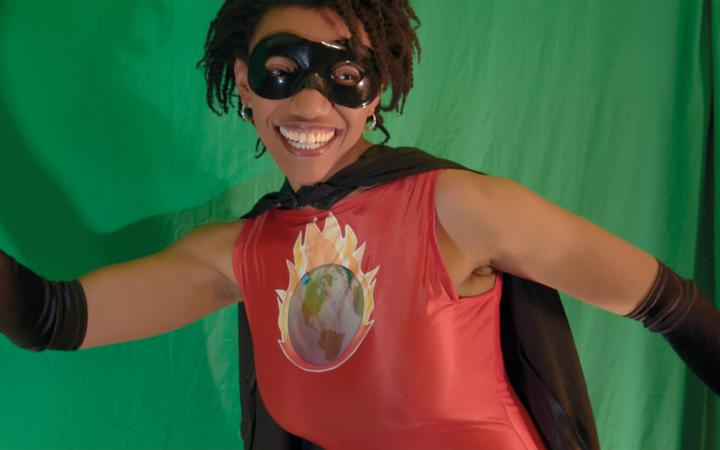 A woman is wearing a superhero costume, smiles and raises her right fist