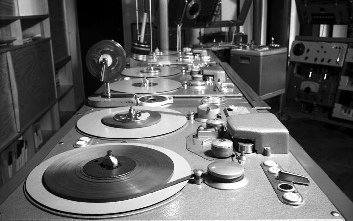 The black and white image shows an old mixing console.