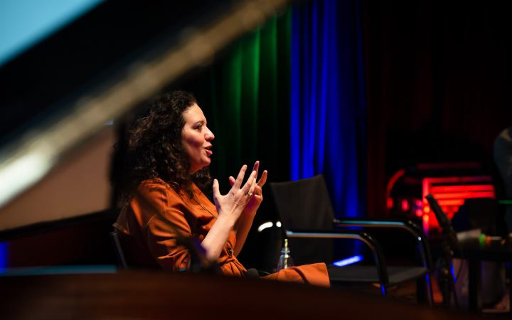 Noa Frenkel in conversation, her hands gesturally supporting her speech.