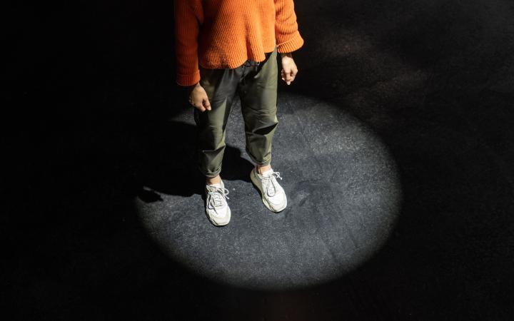 Zu sehen ist eine Person, die auf schwarzem Grund steht und von einem kreisrunden Scheinwerfer angestrahlt wird.