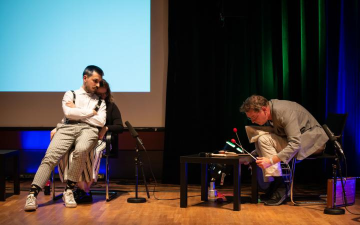 Óscar Escudero sits on the lap of Belenish Moreno-Gil. You listen interested to Manos Tsangaris music, which he creates with sticks