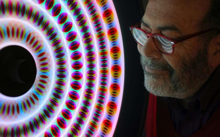 Eine Mann im Profilausschnitt vor einem leuchtenden kreisförmigen Objekt.