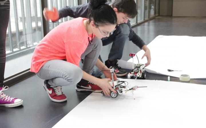 Zwei Jugendliche hocken vor einem großen Bogen Papier und setzen ihre Lego-Roboter gerade auf dem Papier ab.