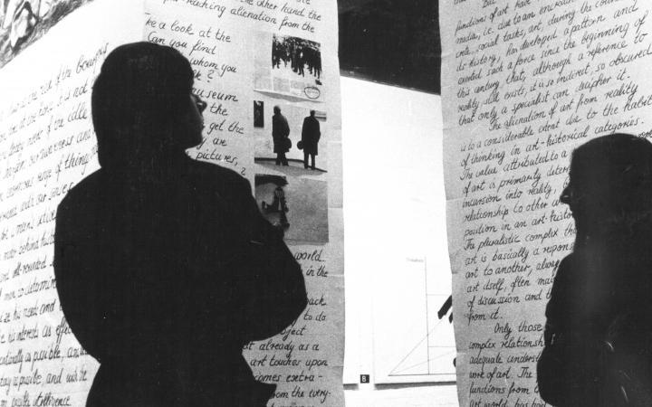 Zwei personen stehen vor Stoffbahnen mit Schrift und Bildern, die von der Decke hängen.