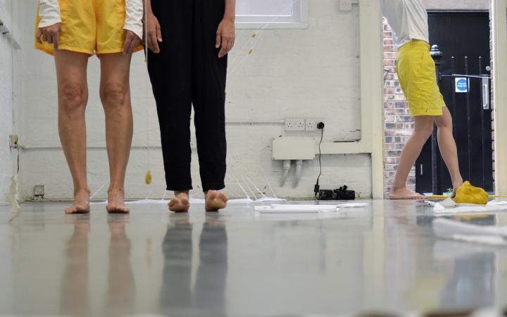 Zu sehen sind vier Beine von zwei Menschen, die nebeneinander stehen. Im Hintergrund sieht man eine Person nach rechts aus dem Bild laufen.