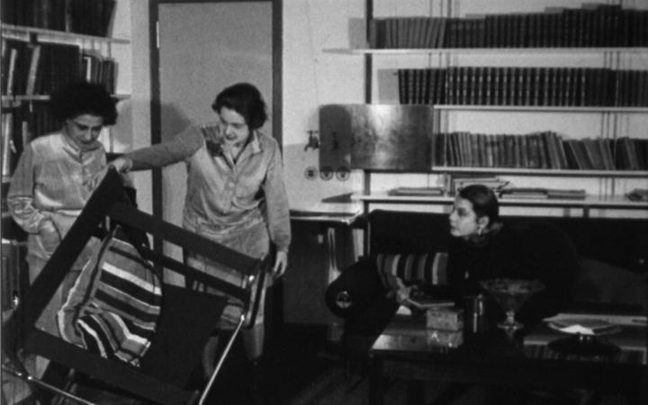 Filmstill aus »Wie wohnen wir gesund und wirtschaftlich?« von 1926 in schwarz-weiß. Darauf sind drei Frauen zu sehen, die die Möbel in einem Wohnzimmer begutachten.