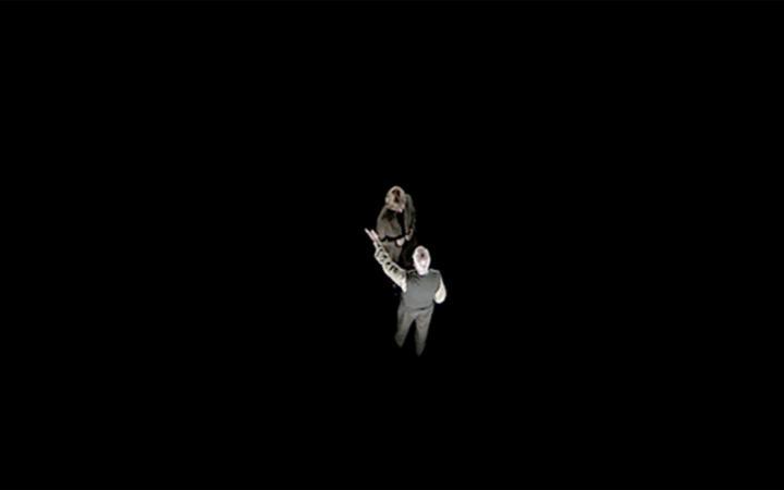 Schwarzer Hintergrund: Blick von oben auf einen Mann und eine Frau im Gespräch