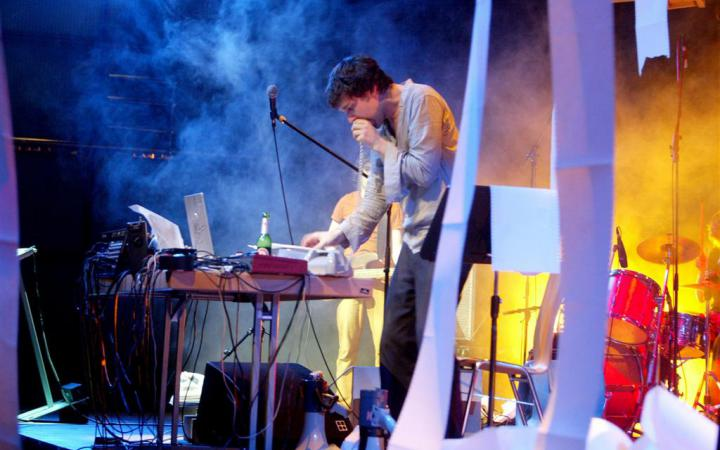 Jamie Lidell performs on stage. From the printers hanging above the stage printers fan-fold paper drops.