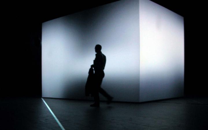 In einem völlig dunklen Raum steht ein 3,5 Meter hoher Würfel, dessen Form durch eine Lichtprojektion verfremdet wird. Davor der Schatten eines Mannes..