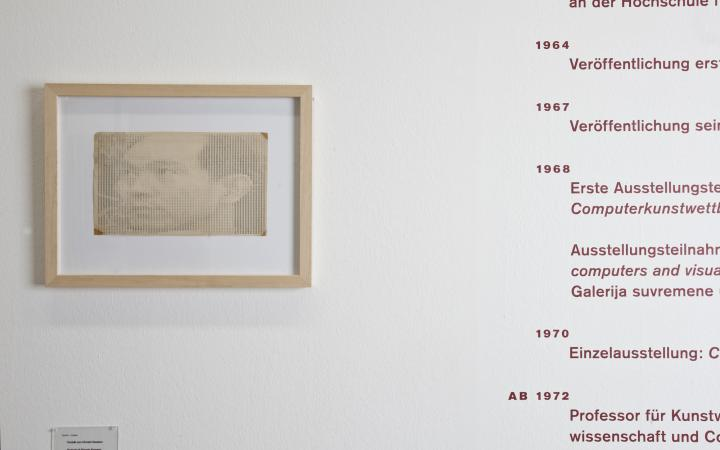 Blick auf eine weiße Wand: Links ein Portrait von Hiroshi Kawano, rechts sein Lebenslauf.