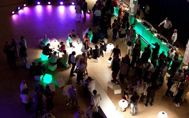 Menschen sitzen in einem abgedunkelten Raum, der in lila und grünes Licht getaucht ist