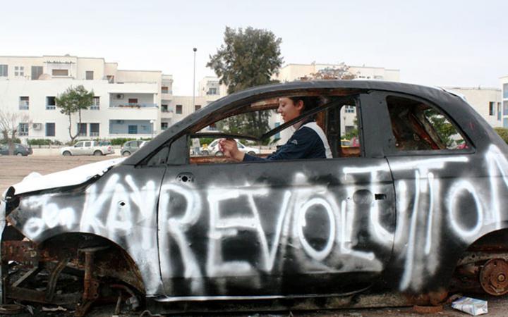 Eine Frau sitzt in einem funktionsuntüchtigen Auto. Auf der Fahrerseite wurde mit weißer Farbe »Revolution« gesprüht.