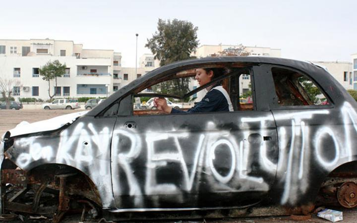 """A woman sitting in a non-functioning car. On the driver's side was sprayed with white color """"revolution""""."""