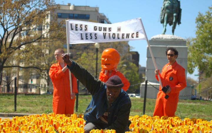 A man in the flower bed raises his right fist as a sign of protest. Behind him, three men with a banner.