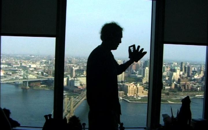 A skyline as a triptych in color. Before that, a man in profile view as a silhouette.