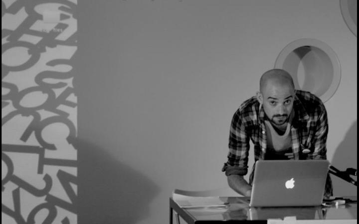 s/w Fotografie. Ein Mann bedient einen Laptop, der auf einem Tisch steht.