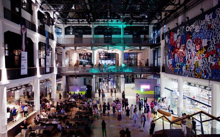 Blick in das ZKM Foyer. Es sind viele Besucher zu sehen. Draußen ist es dunkel. Im Innenraum sind viele farbige Lichtquellen zu deuten.