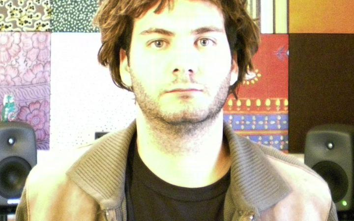 A man in a T-shirt and jacket. In the background two speakers in front of a colored textured wall.