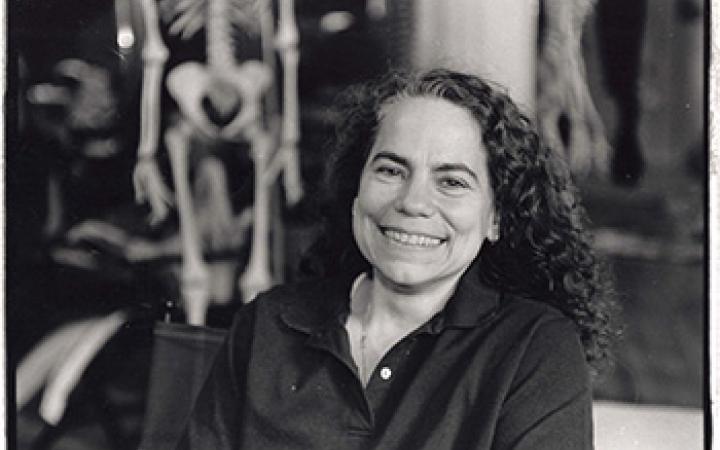 s/w Fotografie. Porträt einer Frau. Im Hintergrund ein menschliches Skelett.