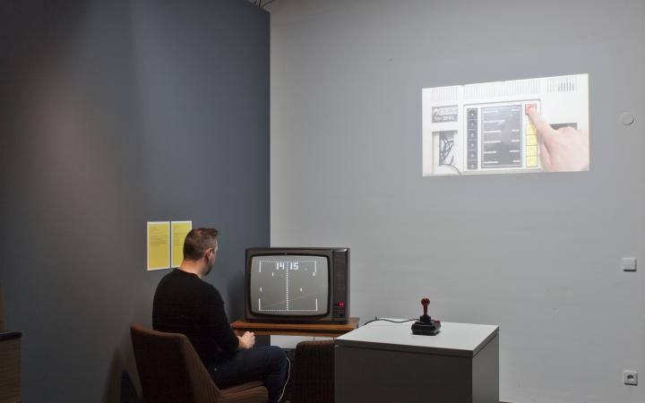 A man sits in front of a TV and plays a video game