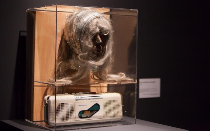A wax-face with hair in a display case