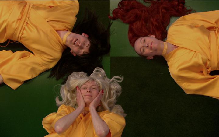 three women, each with blond, black and red hair color lie with their heads together on the floor and looking into the camera