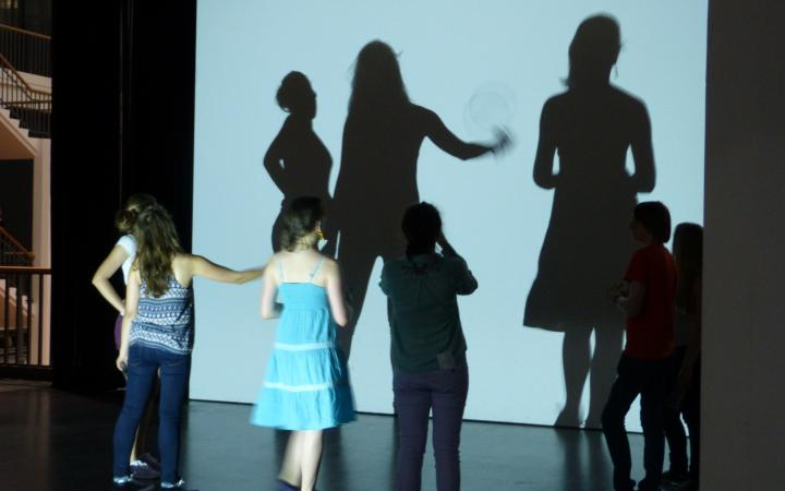 Kinder stehen von einer Wand auf die ihre Schatten fallen