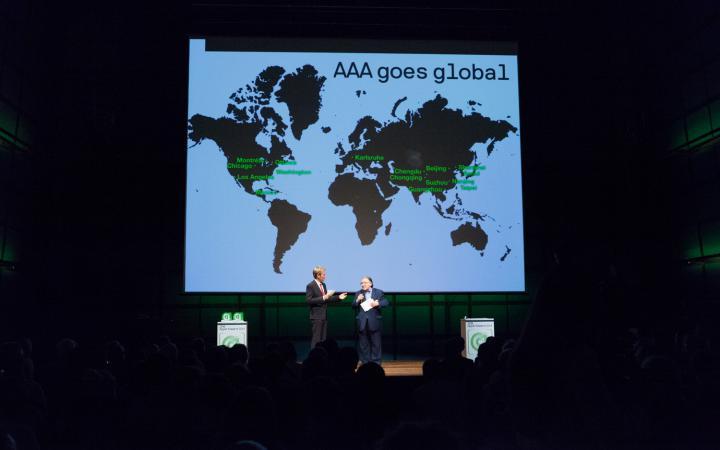 Zwei Männer auf der Bühne. Im Hintergrund eine Weltkarte mit »AAA goes global«