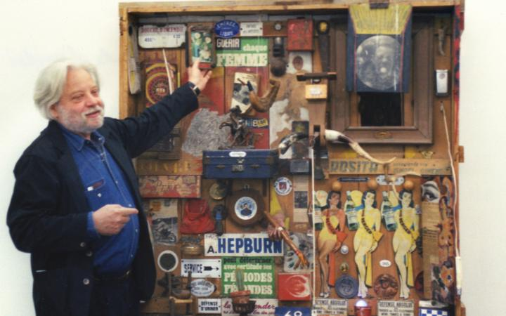 Jean-Jacques Lebel points at a collage