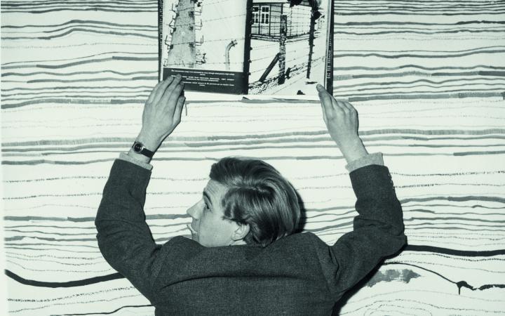 Schwarz-weiß Bild von einem Mann der ein Buch hochhält