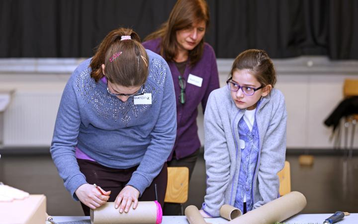 Zwei Mädchen stehen vor einem Tisch mit mehreren Papprollen. Eines der Mädchen markiert gerade die Röhre vor ihr mit dem Stift.