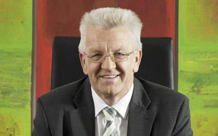 Ein lachender älterer Herr. Er trägt einen grauen Anzug und ein weißes Hemd sowie eine Brille. Seine Haare sind grau. Er sitzt auf einem schwarzen Bürostuhl. Im Hintergrund sind die Farben rot und grün zu sehen.